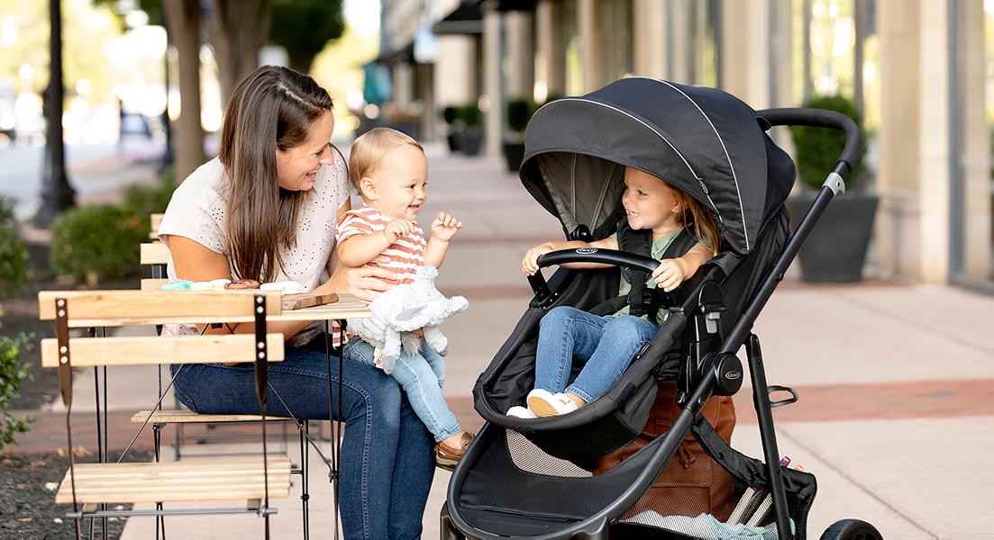 Mutter mit 2 Kindern und dem Kinderwagen Graco Transform